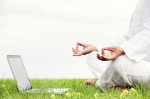 Man sitting in meditative lotus position with notebook